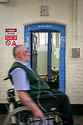 An elderly prisoner goes past his cell in a wheelchair in the vulnerable prisoners unit, which is located on the E wing of the Onslow building at Wandsworth prison. His wheelchair does not fit through his cell door so access is very hard. HM Prison Wandsworth is a Category B men's prison at Wandsworth in the London Borough of Wandsworth, South West London, United Kingdom. It is operated by Her Majesty's Prison Service and is one of the largest prisons in the UK with a population over 1500 people.  (photo by Andy Aitchison)