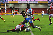 Josh Gordon slides to tackle Bez Lubala during the EFL Sky Bet League 2 match between Walsall and Crawley Town at the Banks's Stadium, Walsall, England on 18 January 2020.