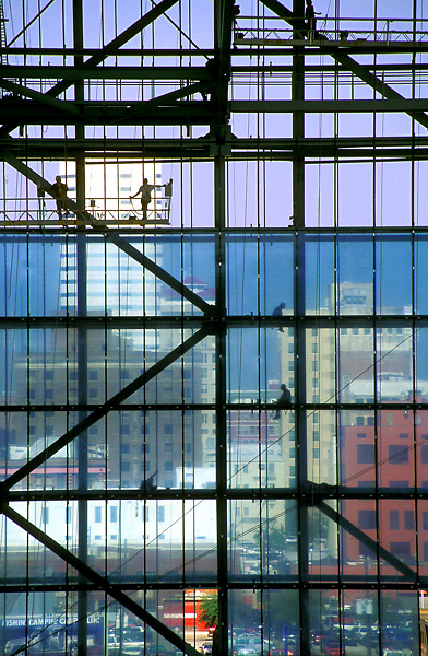 Stock photo of the silhouettes of construction workers on various levels of building frame with downtown buildings in backgraound