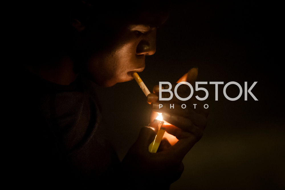 An African migrant lights a cigarrette before heading to France crossing the Spanish-French border walking along Santiago bridge. Irun (Basque Country). August 22, 2018. As the number of migrants arriving on the coasts of southern Spain incresead, more and more migrants are heading north to the border city of Irun. (Gari Garaialde / Bostok Photo)
