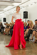 Gown with a red pleated floor-length skirt with long front slit, pleated skirt and eyelet lace white top. By Carmen Marc Valvo at the Spring 2013 Fashion Week show in New York.