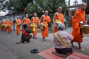 """Mar. 15, 2009 -- LUANG PRABANG, LAOS:  Buddhist Monks in Luang Prabang, Laos, go about their """"Tak Bat,"""" Lao for """"monks morning rounds."""" The monks collect alms in the form of food from people who line their route. For the monks, it is the only food they get that day, for the people it's a chance to """"make merit."""" Luang Prabang is a UNESCO World Heritage Site and the spiritual capital of Laos. There are dozens of """"wats"""" or temples and thousands of monks in the city. It is still the center of Buddhist education in Laos. Photo by Jack Kurtz"""