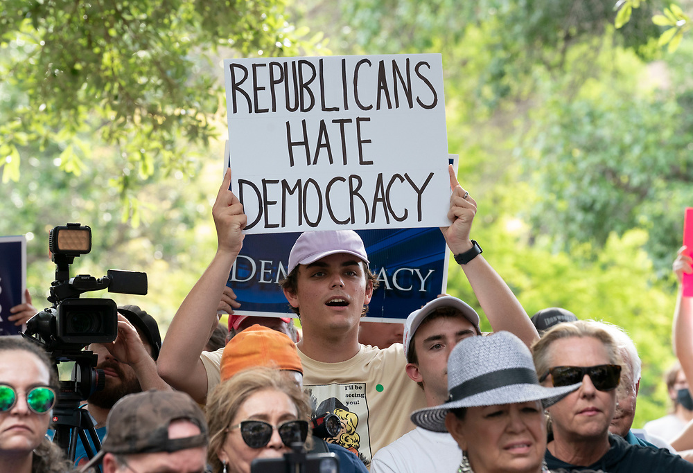 Texas Democrats hold signs denouncing voter supression as almost a thousand Texas Democrats rally at the State Capitol supporting voting rights bills stalled in Congress and decrying Republican efforts to thwart voter registration and access to the polls.