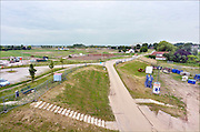 Nederland, Nijmegen, 26-6-2013Aan de overkant van de Waal bij Nijmegen wordt druk gewerkt aan het creeren van een nevengeul in de rivier om bij hoogwater een betere waterafvoer te hebben. het is een omvangrijk project waarbij onder meer 50 huizen gesloopt moesten worden. Op de foto is de sloop, het slopen, nog in volle gang .Measures taken by Nijmegen to give the river Waal, Rhine, more space to flow during highwater.Room, space for the river. Reducing the level, waterlevel. Foto: Flip Franssen