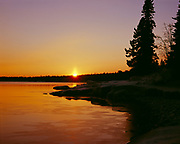 Sun setting over calm waters of Lake Superior during winter freeze-up, Cascade River State Park, Minnesota.