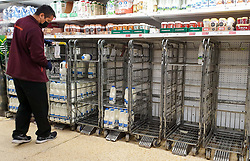 © Licensed to London News Pictures. 21/09/2021. London, UK. A staff member wearing a face covering looks at the empty shelves of fresh milk, just after 8am this morning in Sainsbury's, north London, Fears of food shortages grow after two of the UK's biggest Carbon Dioxide (CO2) producers halted production last week due to soaring gas prices. UK food producers and supermarkets are warning that shoppers are likely to face food shortage caused by a lack of gas could hit this week. Photo credit: Dinendra Haria/LNP