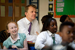 © London News Pictures. 17/07/2013. London, UK.  Minister of State for Schools, DAVID LAWS  listens  year 6 lesson during a visit to St Joseph's Primary School, in Holborn, London with Deputy Prime Minister Nick Clegg (Not pictured). The Government today (17/07/2013) announced plans to rank students nationally at the age of 11.  Photo credit : Ben Cawthra/LNP