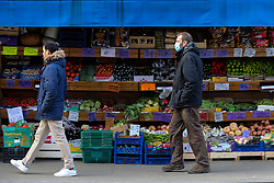 © Licensed to London News Pictures. 25/12/2020. London, UK. People walk past a fruit and vegetable shop in north London, which is open on Christmas Day. Photo credit: Dinendra Haria/LNP