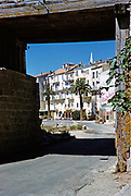 Historic buildings on waterfront framed by archway into town of Calvi, Corsica, France in late 1950s