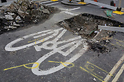 Detail of a bike symbol partially obliterated by roadworks on Tottencourt Court Road, on 3rd August 2017, in London, England.