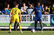 AFC Wimbledon defender Deji Oshilaja (4) taking on Oxford United defender Luke Garbutt (3) during the EFL Sky Bet League 1 match between AFC Wimbledon and Oxford United at the Cherry Red Records Stadium, Kingston, England on 29 September 2018.