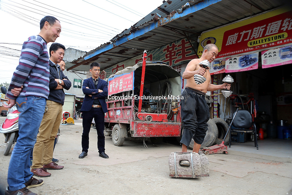 CHENGDU, CHINA - OCTOBER 29: (CHINA OUT)<br /> <br />  55-year-old Man Walks With Over Fifty-kilogram Stone<br /> <br />  Fifty-five-year-old man Huang Baoquan walks with two stones which weigh about 53 kilograms on the street of Qingyang District on October 29, 2015 in Chengdu, Sichuan Province of China. Huang Baoquan has exercised with stones for thirty years and he planed to gain more weight that each stone would reach 50 kilograms.<br /> ©Exclusivepix Media