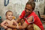 "Mar. 21, 2009 -- BANGKOK, THAILAND:  A woman bathes her infant daughter in an alley in the Monk's Bowl Village. The Monk's Bowl Village on Soi Ban Baat in Bangkok is the only surviving one of what were originally three artisan's communities established by Thai King Rama I for the purpose of handcrafting ""baat"" the ceremonial bowls used by monks as they collect their morning alms. Most monks now use cheaper factory made bowls and the old tradition is dying out. Only six or seven families on Soi Ban Baat still make the bowls by hand. Most of the bowls are now sold to tourists who find their way to hidden alleys in old Bangkok. The small family workshops are only a part of the ""Monk's Bowl Village."" It is also a thriving residential community of narrow alleyways and sidewalks.     Photo by Jack Kurtz"