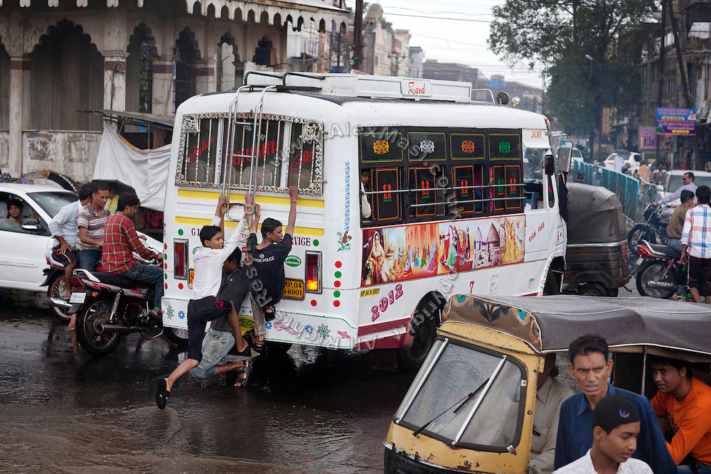 Among heavy traffic, three boys have climbed onto the back of a bus in order to cross a flooded junction in Kasi Camp, one of the nineteen water-affected colonies surrounding the abandoned Union Carbide (now DOW Chemical) industrial complex in Bhopal, Madhya Pradesh, India.