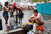 """17 MAY 2010 - BANGKOK, THAILAND: Red Shirt protesters do their laundry on Ratchadamri Road in the Red Shirt camp Monday. Despite promises of a crackdown, a sense of normalcy remains in the Red Shirt camp, which is currently one of the safest places in Bangkok since there have been no attacks or fighting in the camp itself. The Thai government announced Monday that the Red Shirts unofficial military commander and supporter, Thai Army Maj. Gen. KHATTIYA """"Seh Daeng"""" SAWASDIPOL, died Monday from wounds he suffered when a sniper shot him in the head on May 12 while he was being interviewed by an American reporter. When the announcement was read to the Red Shirt protesters still camped out in Ratchaprasong intersection in Bangkok many started weeping.   PHOTO BY JACK KURTZ"""
