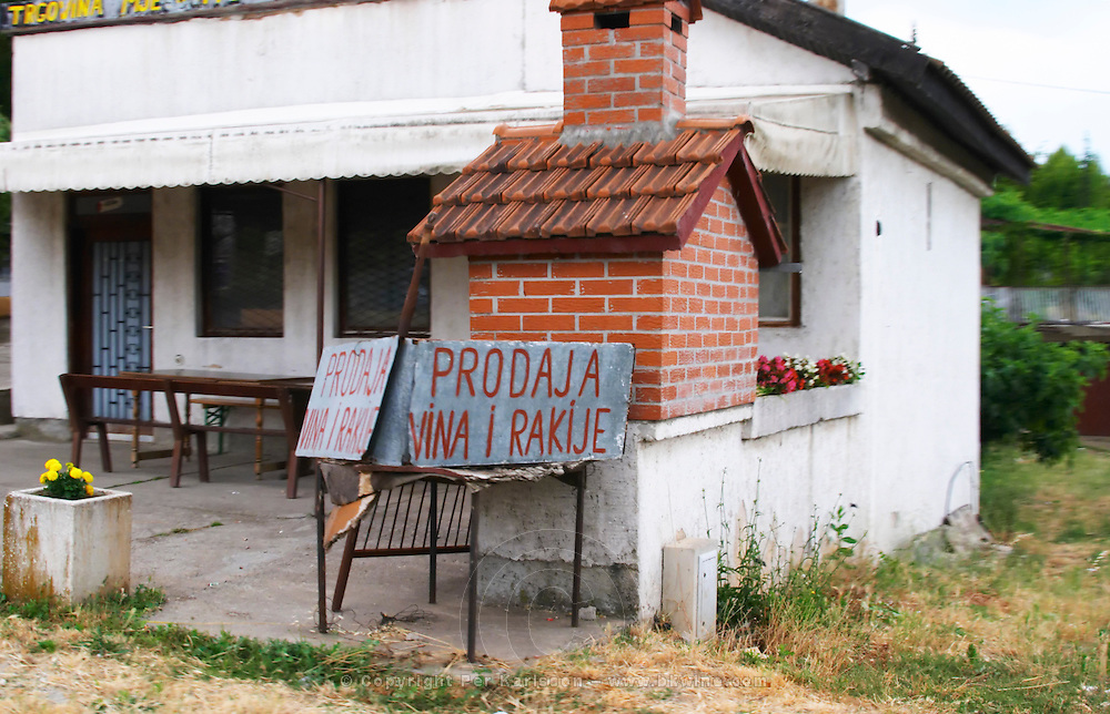 A road side sign advertising the sale of wine and rakija, a grappa type grape spirit. outside a simple restaurant and grill, between Mostar and Citluk. Federation Bosne i Hercegovine. Bosnia Herzegovina, Europe.