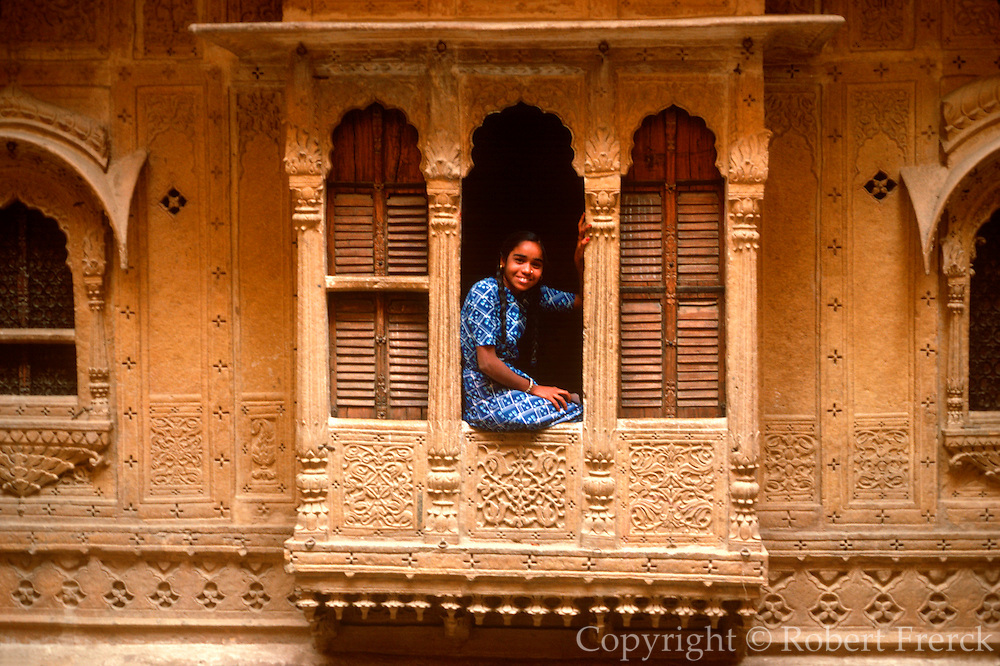 INDIA, RAJASTHAN Girl in a carved window in the city of Jaisalmer