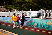 "Women walking to Odongdo island in Yeosu which is connected to the shore by a 768-meter-long breakwater. Yeosu will host the Expo 2012 exhibition  under the theme ""The Living Ocean and Coast"". Yeosu (Yeosu-si) is a city in South Jeolla Province. Old Yeosu City, which was founded in 1949, Yeocheon City, founded in 1986, and Yeocheon County were merged into a new city in 1998."