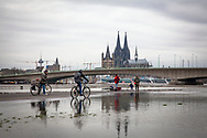flooding of the Rhine on February 5th. 2021, view from the flooded bank of the Rhine in Deutz to the Deutzer bridge, the Cathedral and the church Gross St. Martin, Cologne, Germany.<br /> <br /> Hochwasser des Rheins am 5. Februar 2021, Blick vom ueberfluteten Rheinufer in Deutz zur Deutzer Bruecke, Dom und Kirche Gross St. Martin, Koeln, Deutschland.