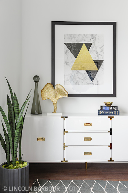 A vignette of some decor inside of an upscale apartment.  A large geometric piece of art hangs over a white credenza with gold handles and brackets.