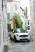Squeezing through - Mini car driving in narrow streets of St Martin de Re, Ile de Re, France