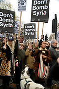 Whitehall November 28th Protest organised by Stop the War against the proposed bombing of Syria. A young woman with a baby on her back holds a placard saying 'Don't bomb Syria ' as do the people she is with.