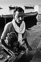 A boatman poses for a portrait after a sunrise boat ride