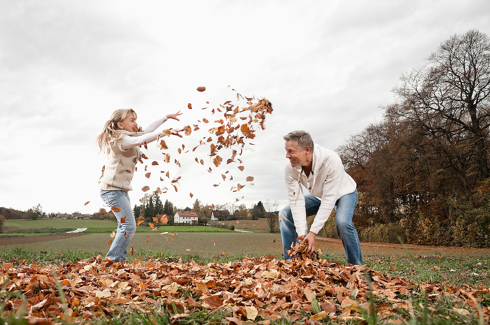 Happy girl with father throwing autumn leaves