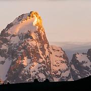 Malachi Artise grabs an air on his mountain bike as the sun rises over Grand Teton in the Teton Range, Wyoming.