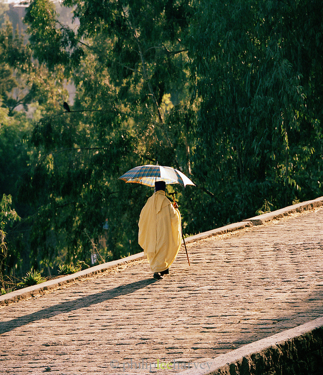 Priest walking up a stone road ramp in Lalibela, Ethiopia