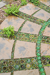 Patio with plants planted amongst paving slabs and decorative use of sunken, upturned bottles and gravel