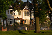 In evening sunshine, a woman runner jogs past suburban houses in the borough of Lambeth, on 7th June 2021, in south London, England.