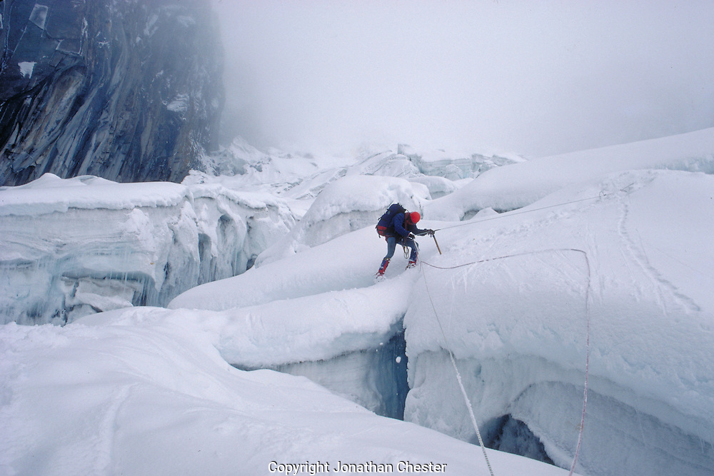 Climber on a fixed rope travereses a crevass while ascending a glacier on the  south side of Annapurna III.