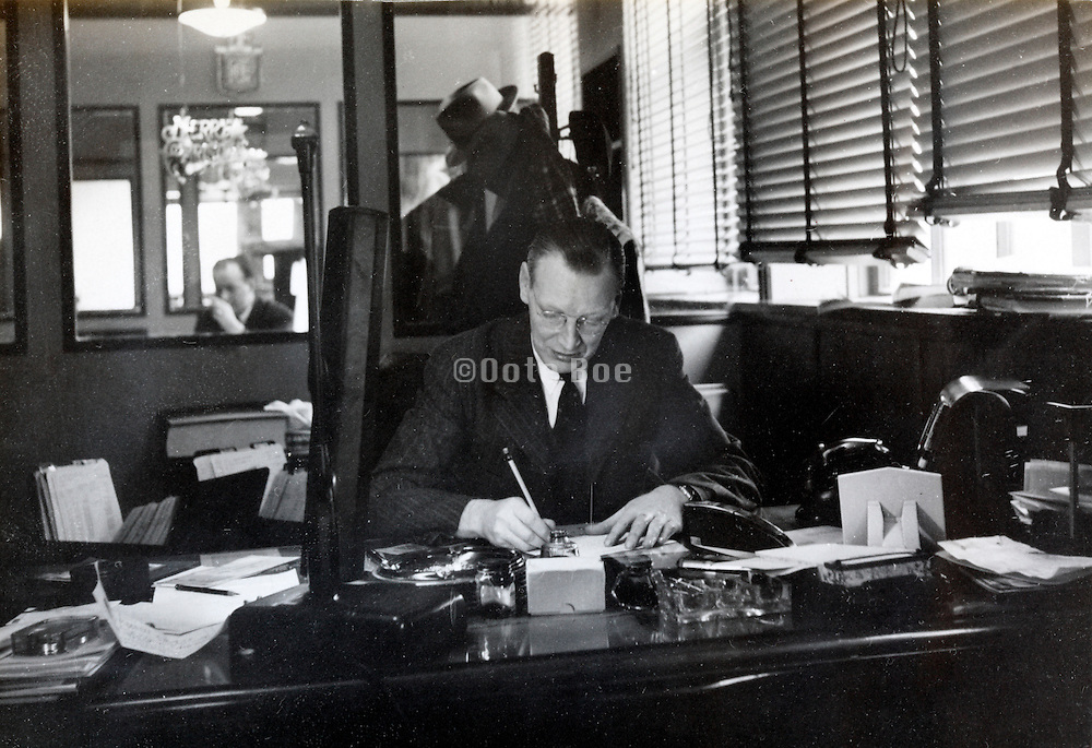 the factory manager sitting and working at his desk USA 1940s