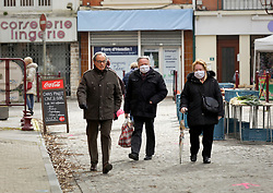 02 April 2020. Hesdin, Pas de Calais, France. <br /> Coronavirus - COVID-19 in Northern France.<br /> <br /> Older locals head to the re-opened street market for their weekly supplies in a slight easing of lock down rules. For the first time since government restrictions came into force, the main market in Hesdin has been permitted to re-open. The historical town has hosted a usually vibrant and bustling market since the Middle Ages. With stall holders limited and many suffering huge financial losses, those selling food today were happy to be back to work despite the ongoing risks posed by coronavirus.<br /> <br /> Shoppers, many wearing masks were mostly maintaining their social distancing with people happy to be out and able to meet and talk with other people. A lot of shoppers were elderly people who have been trapped in their homes for weeks. One shopper complained of 'la misère,' - the misery of this virus and being stuck in her home. <br /> <br /> Anyone leaving their home must carry with them an 'attestation,' in a effect a self administered permit to allow them out of the house. If stopped by the police, one must produce a valid permit along with identification papers. Failure to do so is punishable with heavy fines. Movement in France has been heavily restricted by the government and today's market re-opening was a brief return to normalcy for many able to escape the confines of their homes.<br /> <br /> Photo©; Charlie Varley/varleypix.com