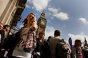 Crowds of British citizens to and fro beneath Gothic tower of Big Ben in Parliament Square.