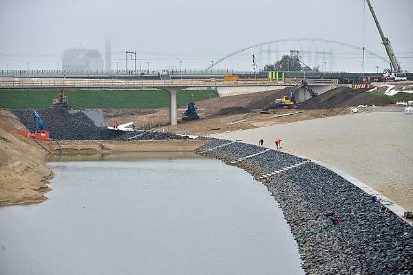 Nederland, Nijmegen, 29-10-2014 Aan de overkant van de Waal bij Lent wordt druk gewerkt aan het creeren van een nevengeul in de rivier om bij hoogwater een betere waterafvoer te hebben. Het is een omvangrijk project waarbij onder meer de pijlers van het spoorviaduct een bredere basis moeten krijgen omdat die straks in de loop van het water staan. Ook de n325 die vanaf de Waalbrug naar Arnhem loopt moet over 400 meter opnieuw worden aangelegd omdat het talud vervangen wordt door pijlers. De weg wordt via een bypass omgeleid. Het dorp veurlent komt op een kunstmatig eiland te liggen met twee bruggen als ontsluiting. Een voetgangersbrug en de andere voor normaal verkeer. Inmiddels begint de nieuwe kade aan de noordkant van deze geul vorm te krijgen. Ruimte voor de rivier, water, waal. In de nieuwe dijk wordt een drempel gebouwd die stapsgewijs water doorlaat en bij hoogwater overloopt. Measures taken by Nijmegen to give the river Waal, Rhine, more space to flow during highwater and to prevent the risk of flooding. Room for the river. Reducing the level, waterlevel. Foto: Flip Franssen/Hollandse Hoogte