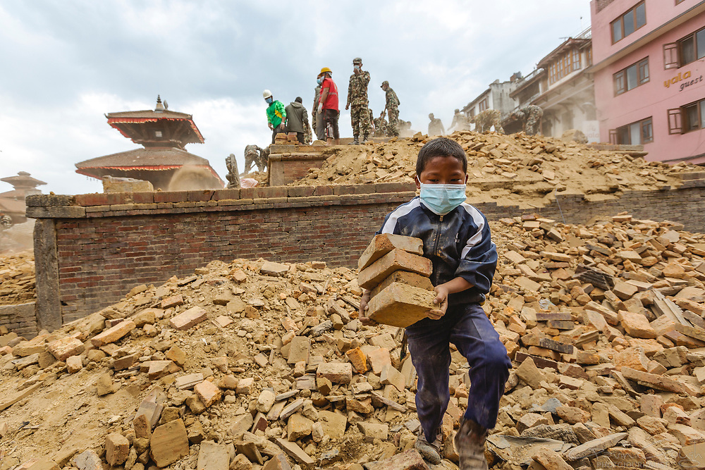 A boy joins relief and recovery efforts, carrying bricks from a temple destroyed by the  2015 Nepal earthquake.