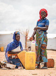 30 May 2019, Mokolo, Cameroon: Women prepare to carry their jerry cans home from one of the distribution points for drinking water in Minawao. The Minawao camp for Nigerian refugees, located in the Far North region of Cameroon, hosts some 58,000 refugees from North East Nigeria. The refugees are supported by the Lutheran World Federation, together with a range of partners.