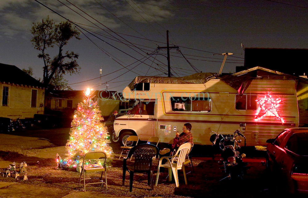 20th, December 2005. New Orleans Christmas decorations. A camper van, the new home of Pijer Day sits outside what was once her home in the flood ravaged Mid City neighbourhood. Pijer erected a tree with a miniature village on the corner of the street to cheer the four residents who have returned to the neighbourhood. All lights powered by generator.