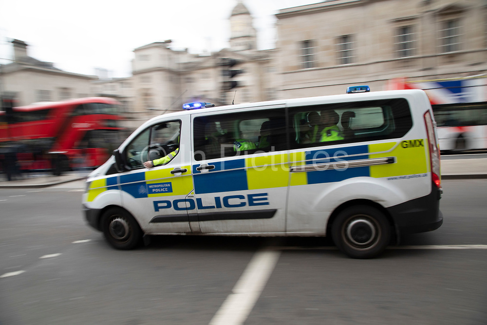 Metropolitan police van passes at speed on Whitehall in London, United Kingdom. The service responsible for law enforcement within Greater London is the Metropolitan Police Service.