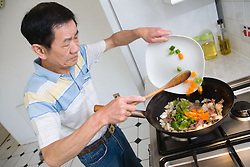Man cooking meal of beef in black bean sauce,