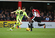 Hudderfield Town striker Joe Lolley and Brentford midfielder Toumani Diagouraga 50\50 during the Sky Bet Championship match between Brentford and Huddersfield Town at Griffin Park, London, England on 19 December 2015. Photo by Matthew Redman.