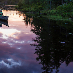 A man canoeing at sunrise on Little Berry Pond in Maine's Northern Forest. Cold Stream watershed, Johnson Mountain Township.
