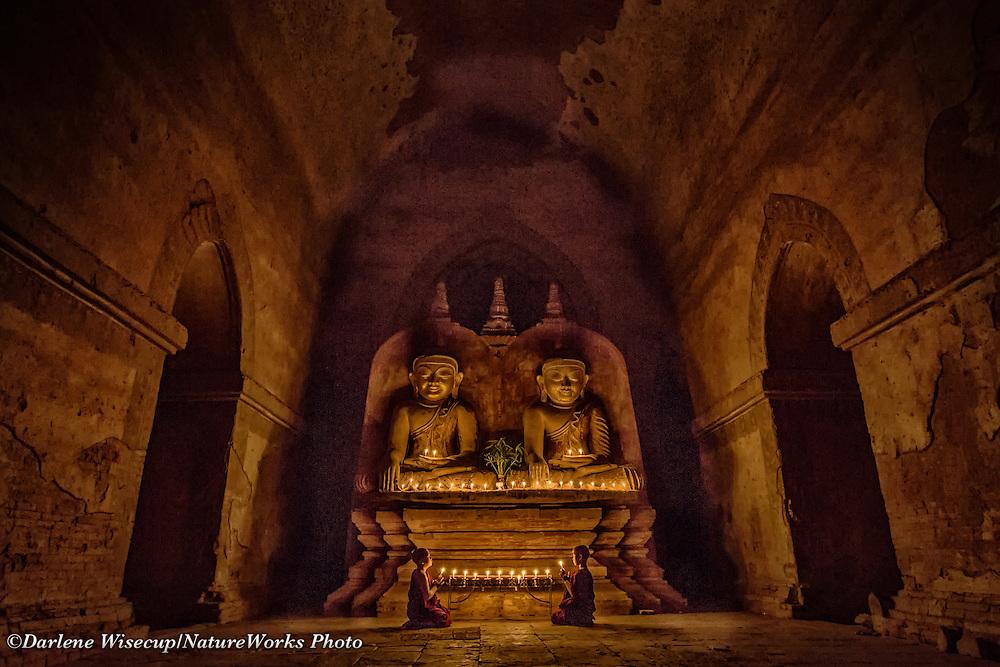 Buddhist novice monks praying in candlelight at Dhamayangyi Temple, Bagan, Myanmar