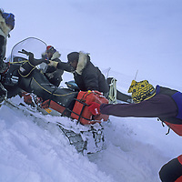 BAFFIN ISLAND, Nunavut, Canada. Alex Lowe pushes Inuit snowmobile carrying expedition equipment to Great Sail Peak.