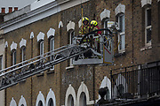Fire fighters attend a fire in premises on the Walworth Road, on 16th January 2019, in London, England. According to London Fire Brigade, Ten fire engines and around 70 firefighters were called to a fire at a shop with flats above on Walworth Road in Walworth. The ground floor of the building was destroyed by the blaze and a small part of the basement, first floor and second floor were also damaged. Firefighters wearing breathing apparatus rescued one man and one woman from a first floor flat roof using a short extension ladder. The woman was treated at the scene for smoke inhalation then taken to hospital by London Ambulance Service crews.