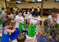 "Volunteers Max Lovisek, Cassie Moorehead, Sue Lowry, Hailey, Caleb and Angel McCarty fill up their ""Got Lunch"" bags during Week 1 at the Congregational Church Monday morning.  (Karen Bobotas/for the Laconia Daily Sun)"