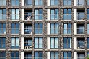 Nederland, Nijmegen, 23-4-2019Woontoren op de Handelskade aan de Waalhaven. Het gebouw staat aan de rand van het stadscentrum en beschikt over luxe koopappartementen, sociale huurappartementen voor jongeren en vrije sector huurappartementen. Het is onderdeel van de nieuwbouw van Nijmegen west, het waalfront. Op het perceel stond voorheen de drukkerij en redactieruimte van regionaal dagblad de gelderlander die nu een verdieping van dit gebouw huren. Een bewoner sit op haar balkon een boek te lezen in de zon . FOTO: FLIP FRANSSEN