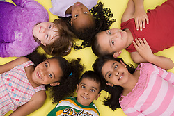 Group of children lying in a circle,